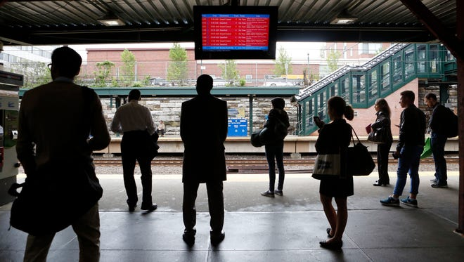 Commuters wait for a delayed train on Friday at the New Rochelle station. New Haven Line trains were restored and running close to schedule after wire repairs delayed trains up to 60 minutes from Harrison to Grand Central.