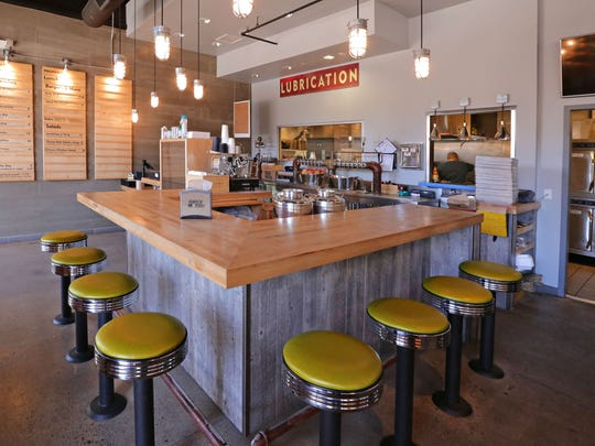 The interior of Nocawich in Tempe has wood-trimmed walls, countertops and tables, with industrial pendant lights, and splashes of lime green on the counter stools.