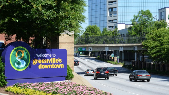 In this file photo, cars drive past a 'Welcome to Greenville's Downtown' sign.