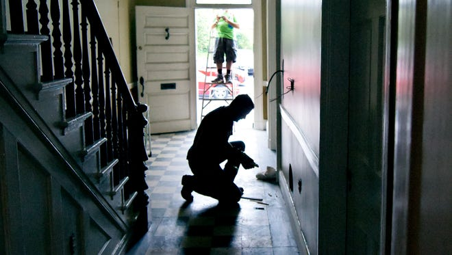 Architectural designer and volunteer Terrence Downs of North York cleans the transom window over the front door while Crispus Attucks construction manager Toby Orwig works on on electrical outlet at the Goodridge Freedom House Friday, May 12, 2016. Workers are preparing the house and Underground Railroad museum for its grand opening May 21 from 1 p.m. to 5 p.m. Bill Kalina photo