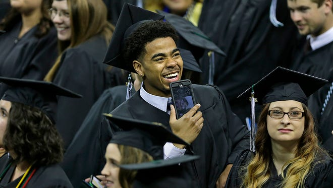In middle, Carrington Love is all smiles as he finds his family in the crowd during the UW-Green Bay commencement ceremony Saturday at the Kress Events Center.6.