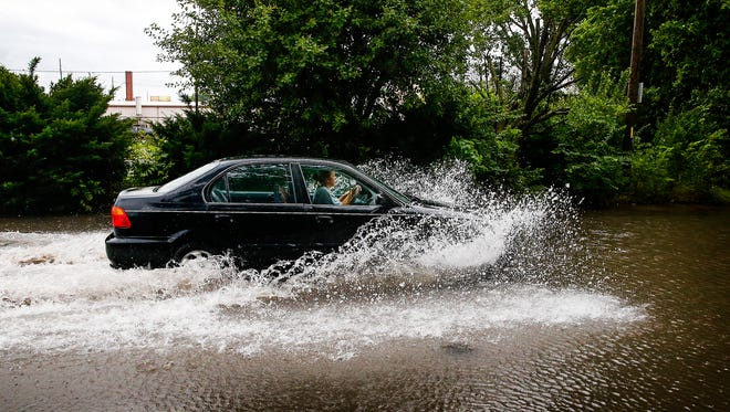 A driver makes her way through standing water on Koehne Street on the west side of Indianapolis on Tuesday, July 11, 2017.