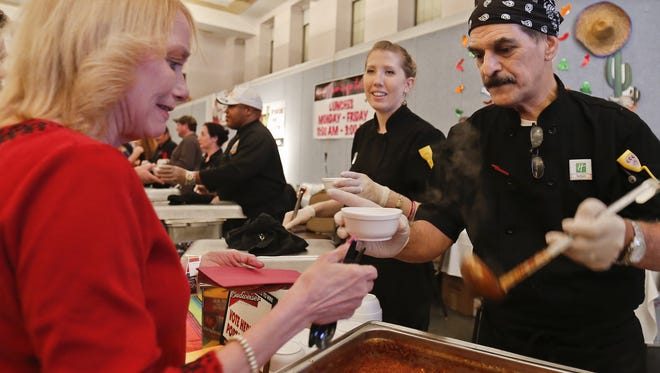 """Sedgie Davis of Holiday Inn serves up some """"Down Home"""" chili to Melanie Lassila during a previous Chili Cookoff."""