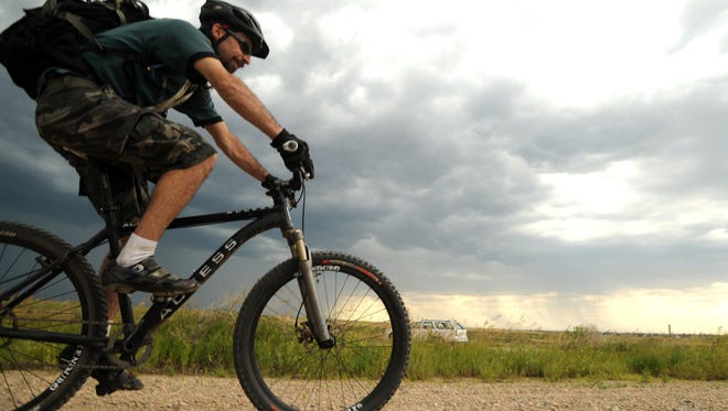 Fort Collins mountain biker A man braces against the wind as he rides at Coyote Ridge Natural Area in June 2013.