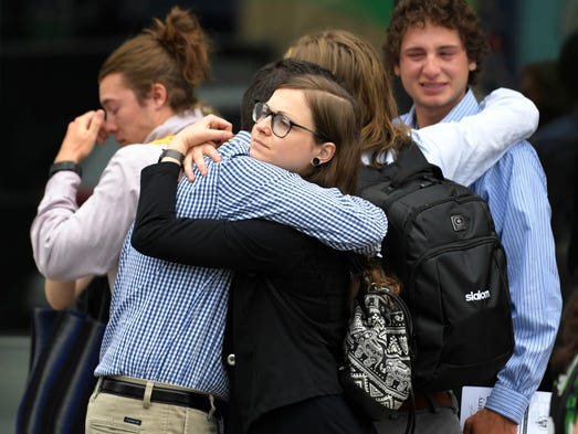 Mourners hug after the memorial service for Max Barry,