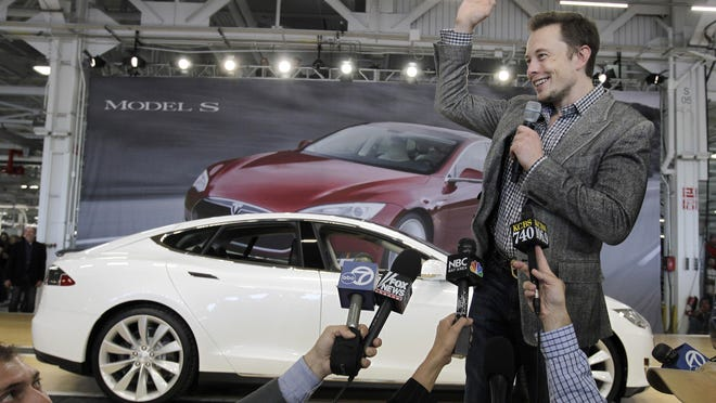Tesla Motors CEO Elon Musk waves during a rally at the Tesla factory in Fremont, California in 2012.