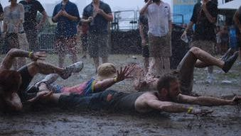 Festivalgoers get muddy after rain delays musical acts at Mo Pop music festival at West Riverfront Park, Saturday, July 25, 2015.
