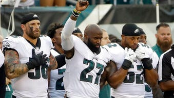 Chris Long (56) puts his left arm around Malcolm Jenkins as Jenkins raises his fist during the national anthem Thursday night.