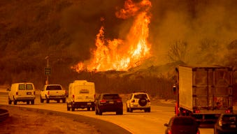 Flames from a wildfire leap above traffic on Highway 101 north of Ventura, Calif., on Wednesday.