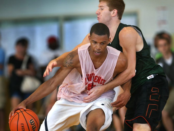 Zionsville High School's Jake Mann defends Lawrence North's Pat Bacon during their game at the high school recruiting event held at Warren Central High School on Saturday, June 21, 2014.