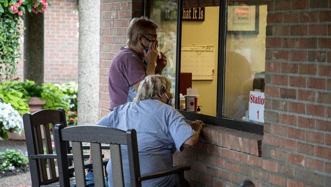 Janet Whittington and her mom, Jane Whiteside, look through a window to watch for her aunt, Shirley Kirk, to be brought into an office room for visitation at SharonBrooke Assisted Living Facility in Newark.