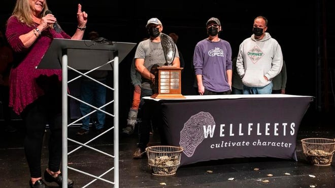 Top Shuckers:  Jodi Birchall presents Wellfleet OysterFest shucking competition awards to three finalists in last Saturday's shuck-off. William 'Chopper' Young, left, won the top prize as fastest shucker. Calen Bricault and Kyle Morse were runners-up. The shuck-off was seen on YouTube.