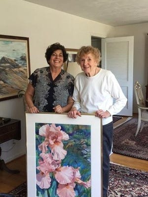 "Jeanne Lindsay and Nan Miller holding ""Iris by the Pond"" and making a final art section at Lindsay's studio for the upcoming ""Visions of Summer"" show."