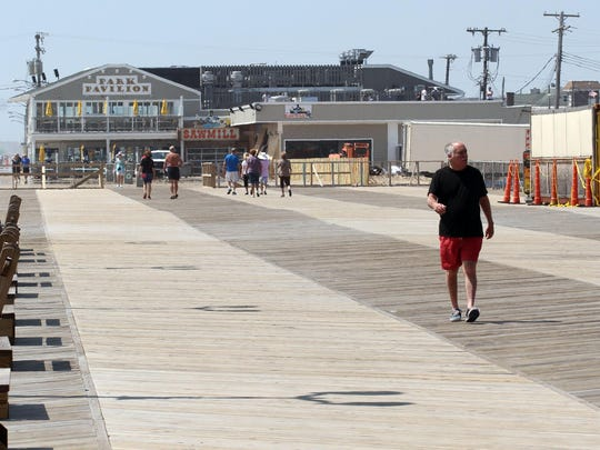 A man walks along the south end of the Seaside Heights boardwalk with Seaside Park shown in the distance.