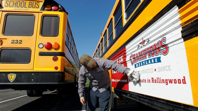 Eanes ISD school bus mechanic Chase Roberts washes the dirt off the advertising on buses in West Lake Hills, Texas, on Feb. 14, 2012.