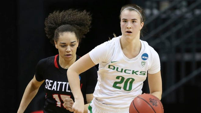 Oregon's Sabrina Ionescu, right, brings the ball down court ahead of Seattle's Kamira Sanders during the second half of a first-round game in the NCAA women's college basketball tournament in Eugene, Ore., Friday, March 16, 2018. (AP Photo/Chris Pietsch)