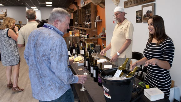 Tiffany Jones, right, and David Carlson serve wine samples from Old Fig Winery at the General Trading Post on East Main Street during the Downtown Visalia Wine Walk on Thursday, April 7, 2016.