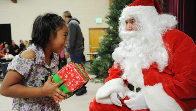 Vianey Zarate, 7, gets a gift from Santa at Thursday's midday Christmas meal at Sacred Heart Church in Salinas.