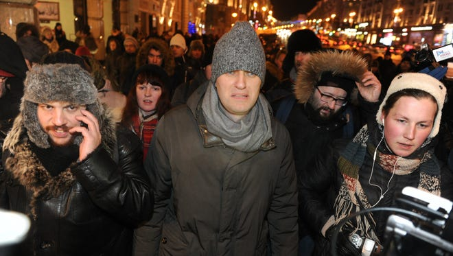 Russian opposition activist and anti-corruption crusader Alexei Navalny, 38, center, walks to attend a rally in Manezhnaya Square in Moscow, Russia, Tuesday, Dec. 30, 2014. The unsanctioned protest came hours after Alexei Navalny was found guilty of fraud and given a suspended sentence.  Navalny, who has been under house arrest since February, is accused of breaking the terms of his house arrest to attend the rally and was detained by police as he approached the site of the protest. (AP Photo/Anton Belitski)