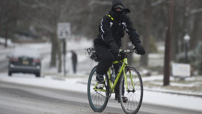 A bicyclist rides along Morris Drive in Cherry Hill. More wintry weather will affect the area Monday morning.