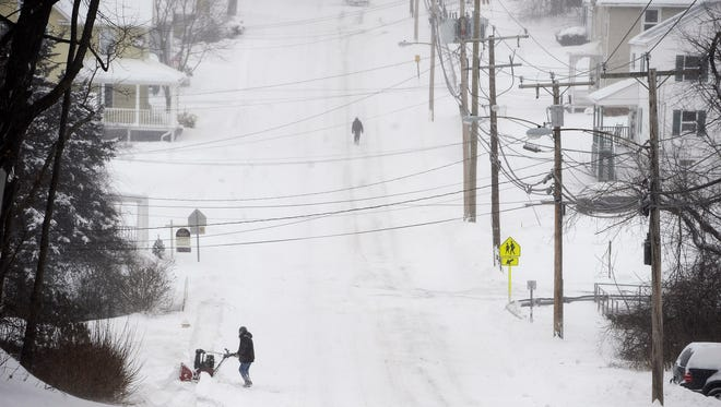 A man clears a path with a snowblower during a snowstorm Tuesday, Jan. 27, 2015, in Windsor Locks, Conn.  A major winter storm dropped a foot of snow or more over much of Connecticut, hitting hardest in the eastern part of the state.