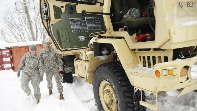 Spc. Elizabeth Limerick and Sgt. Joshua Ferguson walk by an LMTV in the parking lot where the vehicles for the 116th Infantry Brigade Combat Team are parked outside of the National Guard Armory on Thursday, Feb. 13, 2014, in Staunton. The National Guard brigade patrolled the roads on Thursday to help those stranded on the roads and to provide assistance for local first responders.
