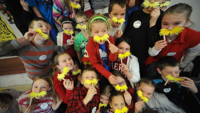 """Kids sport """"Lorax"""" mustaches in honor of the Dr. Seuss character."""