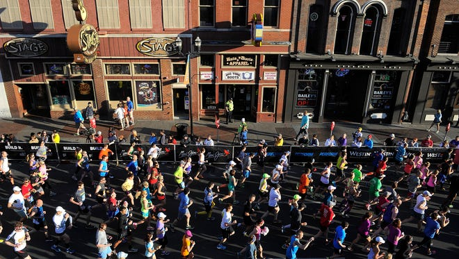 Runners pass by the honky-tonks of lower Broadway as they begin the Country Music Marathon in 2014.