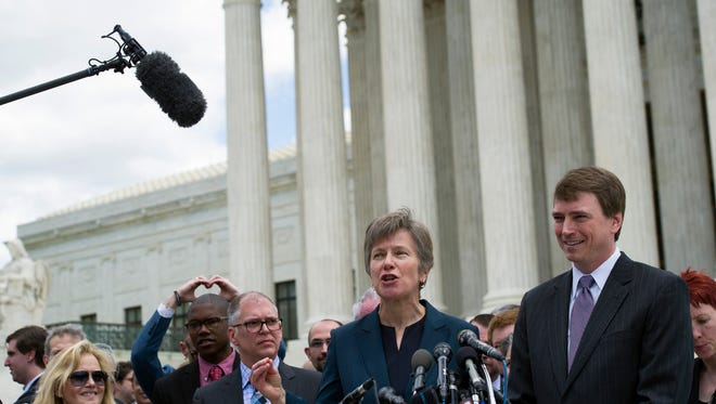 Civil rights lawyer Mary Bonautu, center, flanked by plaintiff James Obergefell of Ohio, left, and Washington attorney Douglas Hallward-Driemeier, right, speaks outside the Supreme Court in Washington, Tuesday , April 28, 2015, following a hearing on same-sex marriage.