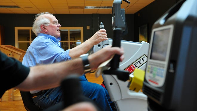 H. W. Tanney tries out the exercise machine in the therapy gym at the open house for the brand new NHC Place, Sumner.