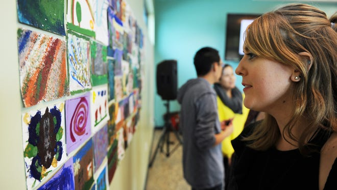 CSUMB art student Katelyn Palmer takes in Wednesday's art opening at the Cesar Chavez library.