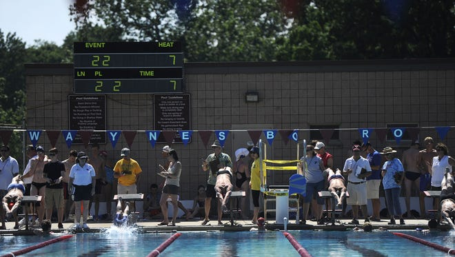 Swimmer's dive off the blocks at War Memorial Pool in Waynesboro while volunteers record times behind them.