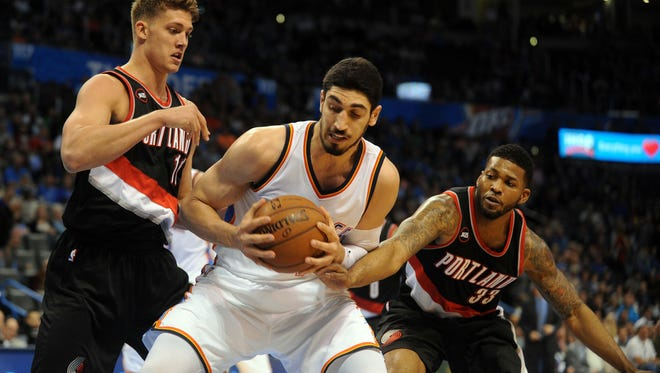 Oklahoma City Thunder center Enes Kanter (34) drives to the basket against Portland Trail Blazers center Meyers Leonard (11) and Portland Trail Blazers forward Alonzo Gee (33) during the fourth quarter at Chesapeake Energy Arena.