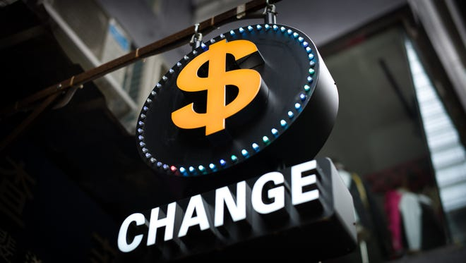 A currency sign is seen in Hong Kong on August 11, 2015.  China's central bank cuts the reference rate for its yuan currency against the US dollar by almost two percent, reportedly a record reduction, as it seeks to bolster flagging economic growth.