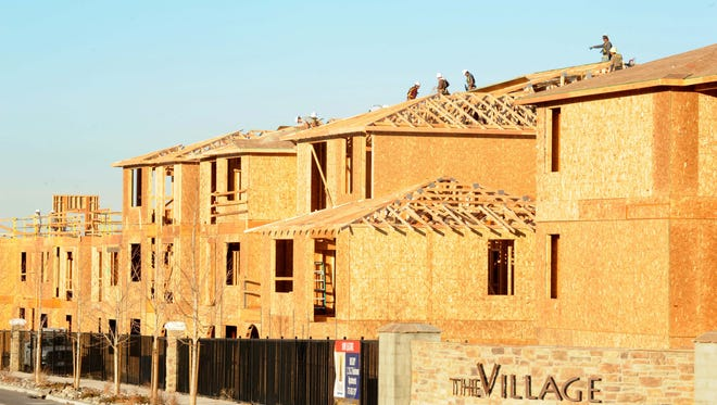 Construction crews work on the roof of luxury apartments on Arrowcreek Parkway.