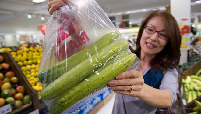 A shopper holds up a bag of cucumbers.