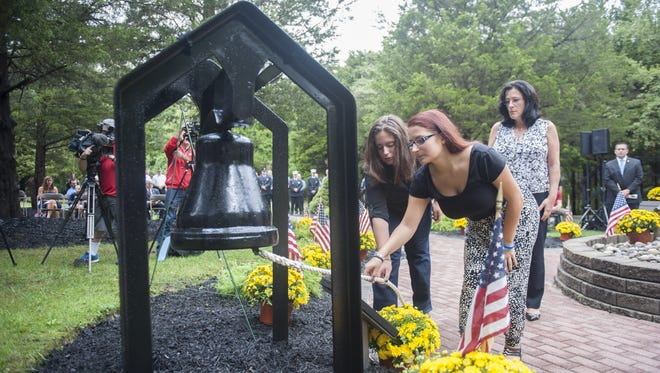Joyce Rodak looks on as her daughters Devon (right) and Chelsea Primavera (left) ring the first bell representing Flight 11 crashing into the North Tower at 8:46 a.m. during the Patriot Day memorial ceremony at Chestnut Branch Park's Place of Reflection in Mantua Twp. The Rodak's lost their husband and father, John Rodak, who was killed in the September 11th attacks in 2001. Friday, September 11, 2015.
