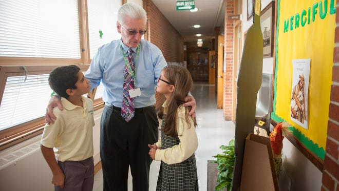 Principal Frank McAneny speaks with 3rd-graders Chase Caulder and Lilly Shreeve at Our Lady of Good Counsel School in Moorestown. This private school was one of only two in South Jersey which recently earned a National Blue Ribbon School distinction from the U.S. Department of Education. Friday, October 9, 2015.