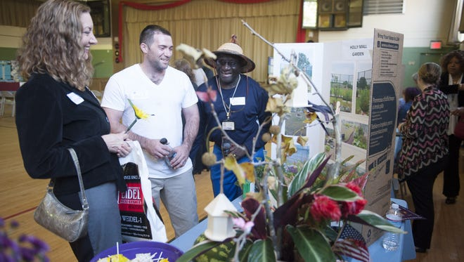 Patient Charles Burnett (center) and Recreational Program Therapist Isaac Ajayi talk with Social Services Administrator Cynthia Vetrano as Burnett shows examples of his work in the Holly Mall Garden during an open house at Ancora Psychiatric Hospital.