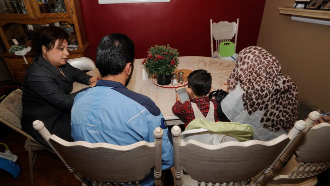 Jeralda Hattar, director of Immigration and Refugee Services for Catholic Charities of Southeast Michigan Family, left, talks with Mahmoud Karaz and his wife, Khairat, and son Ammar Karaz, in Dearborn. For Karaz, there is no going back to Syria.