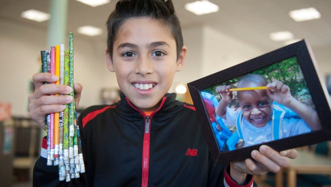 Rice Elementary School fifth-grader Leo Aguilar holds some of the pencils that were collected to send to a remote section of Kenya and a photo of a boy holding a pencil from last year's donation.