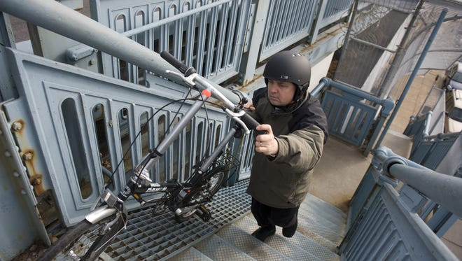 John Boyle, 47, of Edgewater Park, member of the Bicycle Coalition of Greater Philadelphia, walks his bike up to the steps to the Ben Franklin Bridge, the site of a proposed walkway ramp project that will make bridge access much easier for riders. Friday, February 10, 2012.