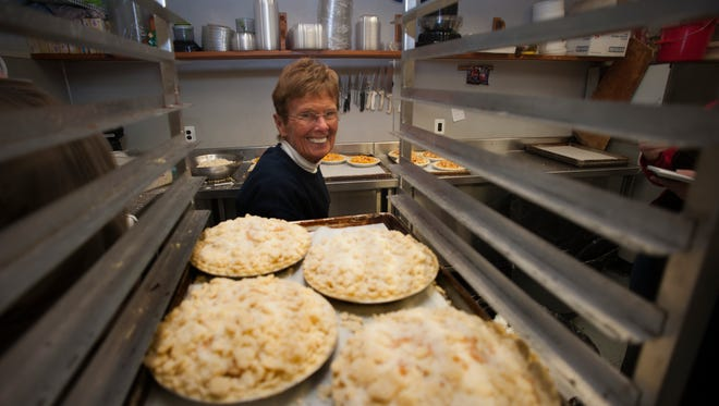 Lois Budd smiles near a stock of pies waiting to be baked  and ready to be packed for the Holiday sale at their store in Woodbury.