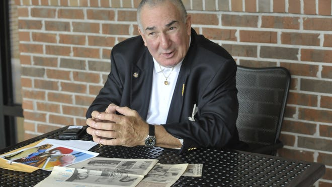 Marty Libowsky sits on the back patio at the Ronald McDonald House of Northwest Florida on Bayou Boulevard and looks through old photos and newspaper clippings that detail his lifetime of volunteer work.