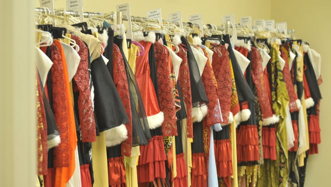 """One of many racks of costumes for the Pensacola Children's Chorus lines the wall of a small dressing room on the first floor of the Saenger Theatre on Palafox Place. Almost 5,000 individual costume pieces will be incorporated into this year's """"Christmas on the Coast,"""" opening on Friday night."""