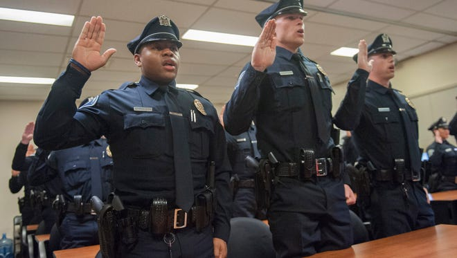 20 new officers including Rodney Banks (left) of Somerdale and Will Clements of Pennsauken take the oath of office and are sworn in during a ceremony at the Camden County Police Department in Camden. Tuesday, December 22, 2015.