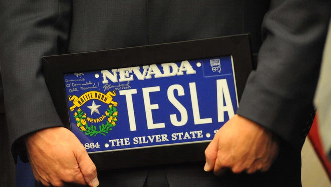 File photo: Diarmuid O'Connell, Tesla vice president of business development, holds a gift presented to him by Nevada Gov. Brian Sandoval after the carmaker's record-breaking agreement with Nevada was announced in 2014.