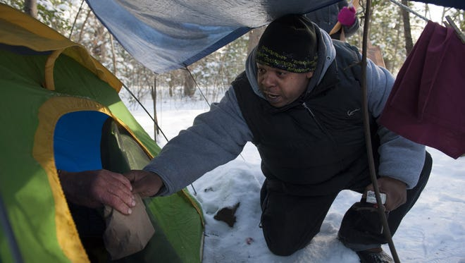 McNeil Byers with Collaborative Support Program NJ, a homeless outreach organization, gives a bag lunch to Robert, a 69-year-old homeless Navy Veteran, at his camp site in a wooded area in Berlin during the 2014 survey.
