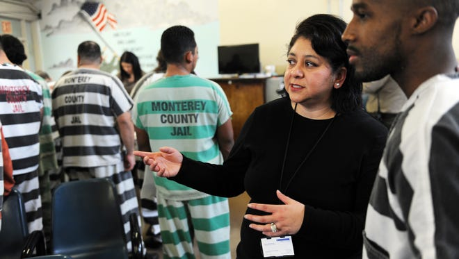 Beatriz Vera-Morga, a substance abuse therapist with BI Incorporated-Monterey County DRC, directs an inmate at Thursday's job fair held Thursday at the Monterey County Jail.
