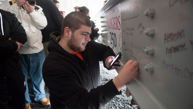 Rutgers-Camden first-year nursing student Dom Rocco, of Marlton, signs a steel beam during a ceremony for the university's Nursing and Science Building.